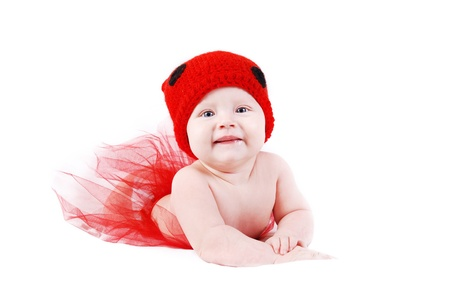 Adorable baby girl in red tutu and ladybug hat lying on white background photo