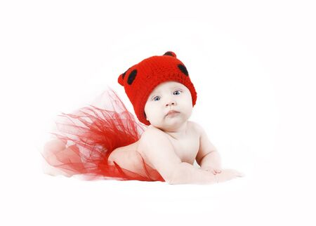 Lovely baby girl in ladybug hat and red tutu lying over white background Stock Photo - 13115583