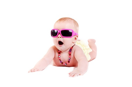 summer wear: Pretty baby girl in pink sunglasses and colored necklace lying on white background  Stock Photo