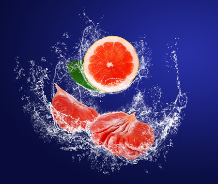 Red guicy pieces of grapefruits with leaves in water splahes on the dark blue background photo