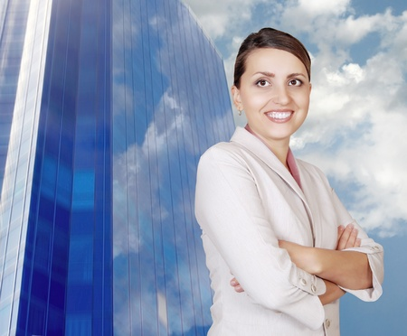 Attractive smiling woman on the bright blue business building and sky background photo