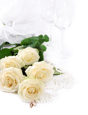 Closeup image with white roses, bridal rings and vine goblets photo