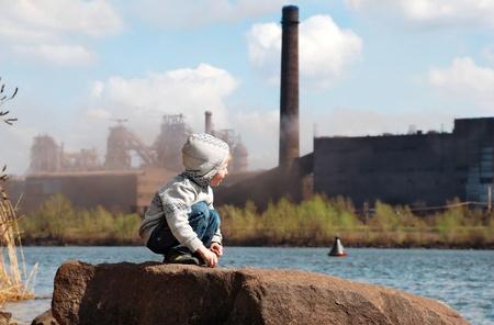 contaminacion del agua: Jugando niño pequeño en la costa del río frente a la planta metalúrgica
