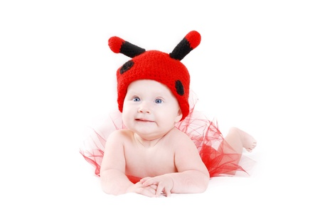 Little baby girl in funny ladybug hat and red tutu lying on white background photo