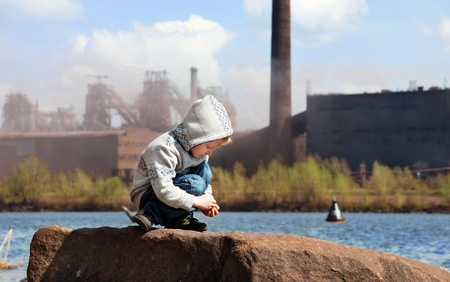 Playing little boy on the river coast in front of metallurgy factory