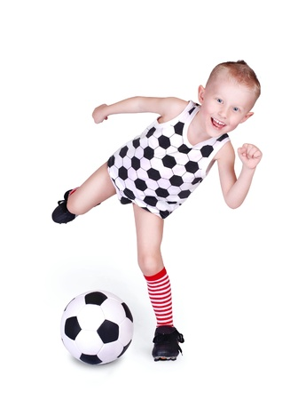 Pretty little boy hits a soccer ball over white background photo