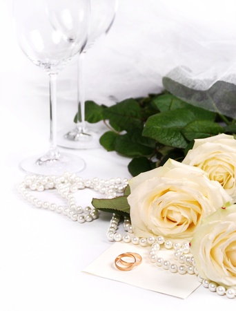 Still life with white roses, pearls and wedding rings photo