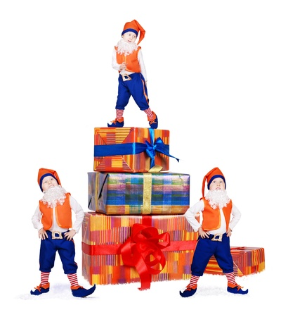 Three posing little gnomes near gift boxes in snow photo