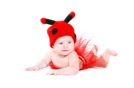 Adorable baby girl in funny ladybird hat and red tutu lying on white background photo