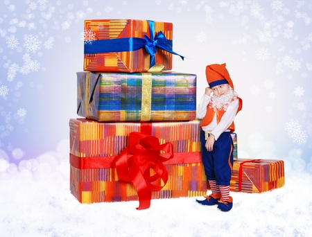 Little gnome with christmas gift boxes on light blue snow background photo