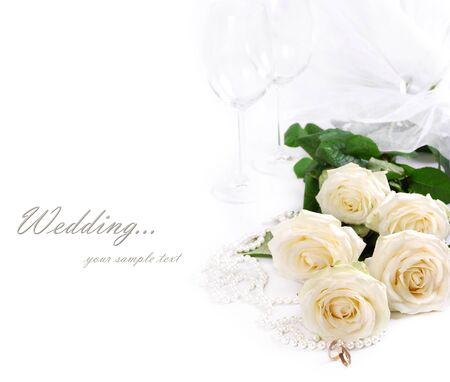 Wedding still life with white roses, golden rings, pearls and goblet photo