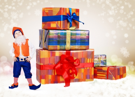 Happy smiling little gnome looking on christmas gifts over light beige background photo