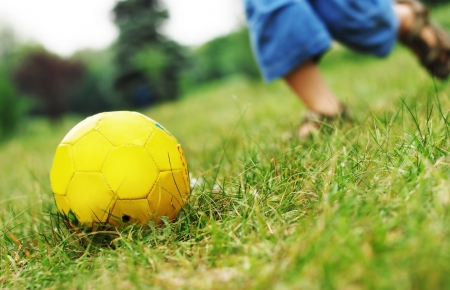 close up image: Image with local focus on yellow ball and running boy  legs Stock Photo