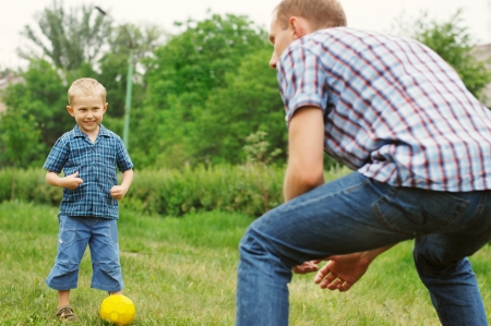 Father training his little son play in football photo