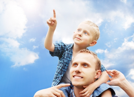 Little son at father's shoulders on blue sky background photo
