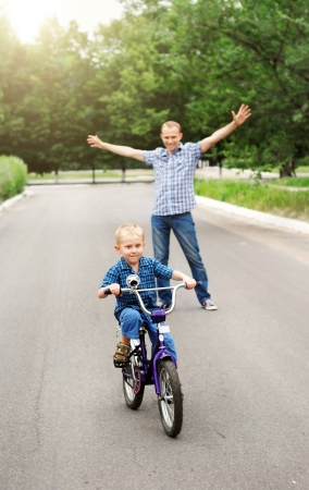 Happy father is train his son to ride a bicycle  photo