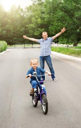 ni�os en bicicleta: Padre feliz es entrenar a su hijo a andar en bicicleta Foto de archivo