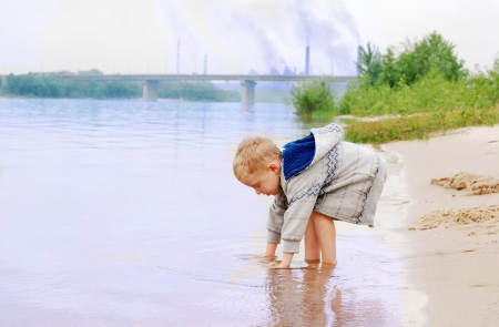 warm water: Playing little boy on the river coast near industrial plant Stock Photo