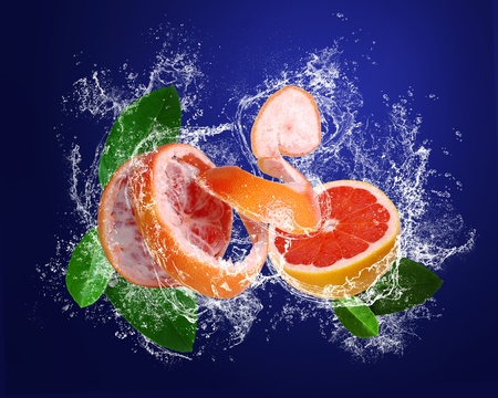 Grapefruits with leaves in water splashes in water splashes on the dark blue background photo