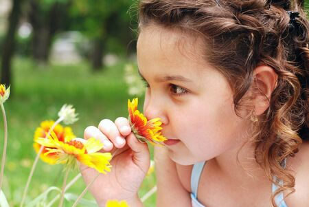 Pretty little girl portrait smelling yellow flower photo