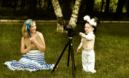 Young lady with book like Alice and little boy like White Rabbit at the green meadow Stock Photo - 14019154