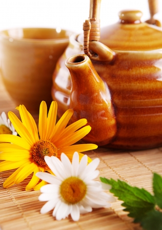 Closeup image of teapot and daisy flowers on the bamboo mat photo