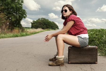 Yong girl - auto stop traveller sitting on old suitcase on the lonely route photo