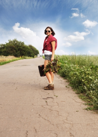 Girl auto-stop traveller with old suitcase on the road photo