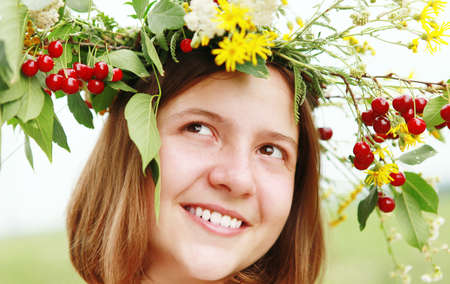 Portrait smiling pretty girl in garland with wild flower and cherry Stock Photo - 14204076