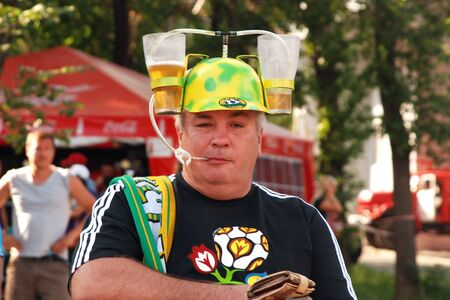 DONETSK, UKRAINE - 27 JUNE 2012: Fottball fan in funny hat with bear glasses. Donetsk, Official fan zone before start match Spain - Portugal. EURO 2012 in Ukraine, 27 june 2012