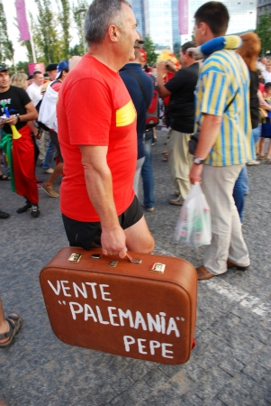 DONETSK, UKRAINE - 27 JUNE 2012: Spanish football fan with vintage suitcase before start semifinal match Spain - Portugal. Donetsk, Donbass Arena. EURO 2012 in Ukraine, 27 june 2012