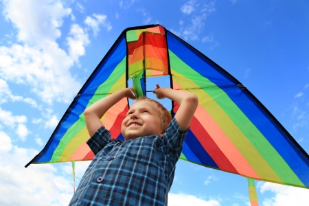 Boy with bright kite over the head on the blue sky view photo