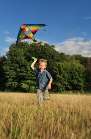 volar: Niño feliz corriendo con colores brillantes cometas en el fiield