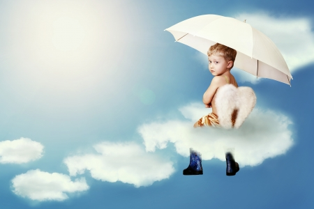 Little boy with angel wings sitting into the cloud on the sky photo