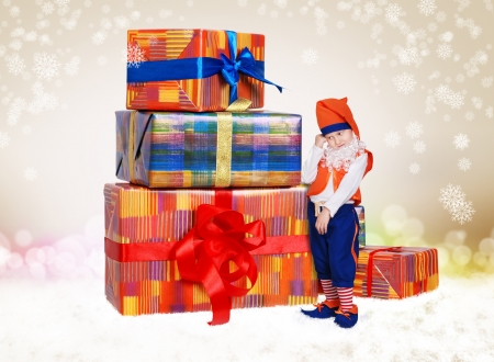 Pretty little gnome with chrismas gifts on light shiny background photo