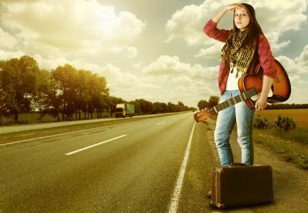 mujer hippie: Yong Chica con guitarra y una maleta vieja en la carretera en la puesta del sol