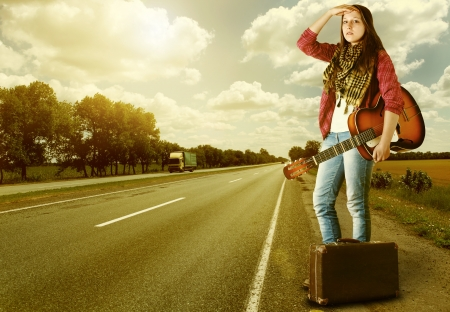 tourists stop: Yong Girl  with guitare and old suitcase at the highway in sunset time