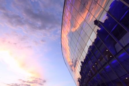 Modern glass building with reflected evening city and sunset sky in it photo