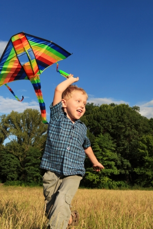 Happy little boy playing with bright kite at the outdoor photo