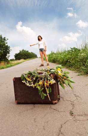 mujer con maleta: Cierre maleta vieja imagen en la carretera con chica - auto-stop viajero