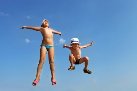 kids playing beach: Happy jumping children in blue sky Stock Photo