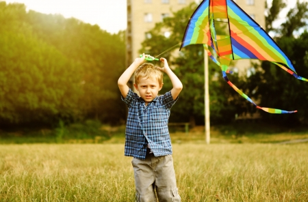 Little boy with kite flying over his head  photo
