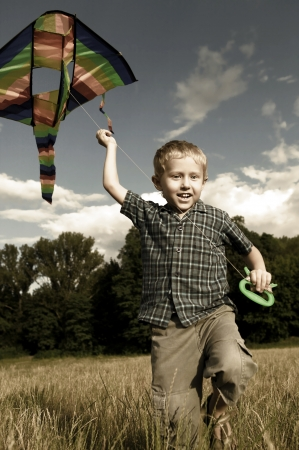 Little boy with rite flying over his head running across the field photo