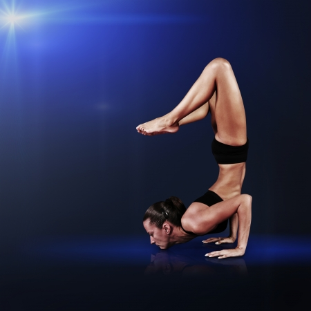 Young woman doing yoga asana on blue abstract backround photo