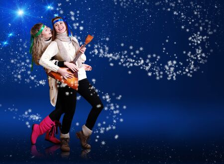 Happy dancing girls with folk elements over dark blue background with snow and stars photo