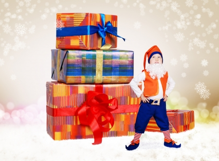Little funny christmas elf looking up on gift boxes photo