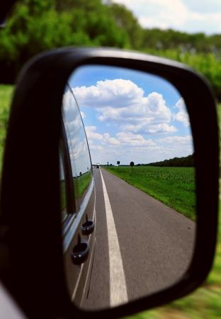 spiegelbeeld: Close-up beeld van achteruitkijkspiegel met snelweg reflectie op het