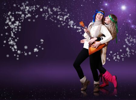 Happy girls with balalika dancing over purple background with snow flakes photo