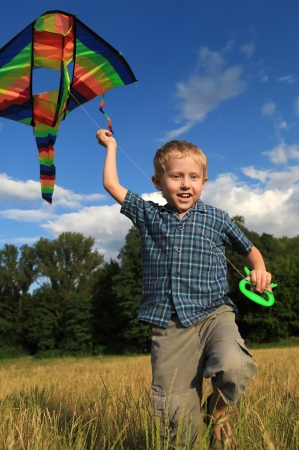 Playing with kite little boy in sunny summer day photo