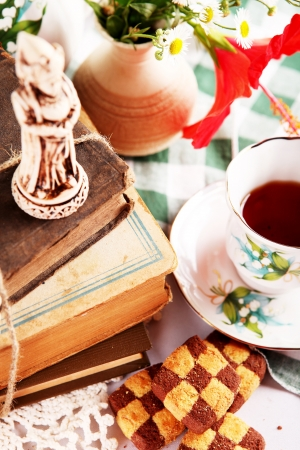 Still life with checkerboard cookies, old books; chess sculpture and cup of tea photo